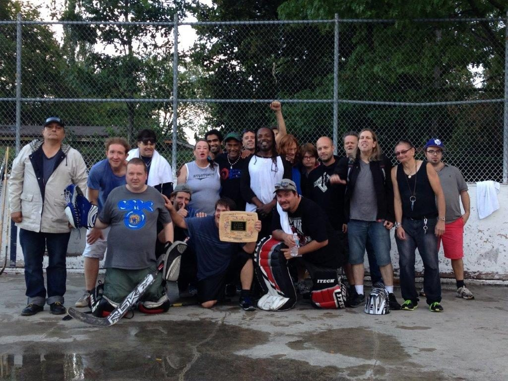 F.R.E.S.H. ball hockey group participants posing for photograph at a ball hockey rink.
